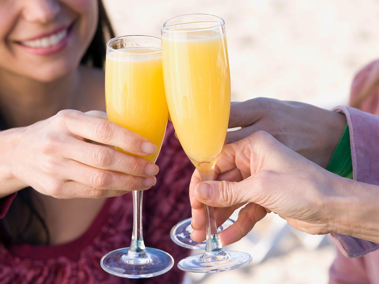 Personnes trinquant avec des verres de mimosa